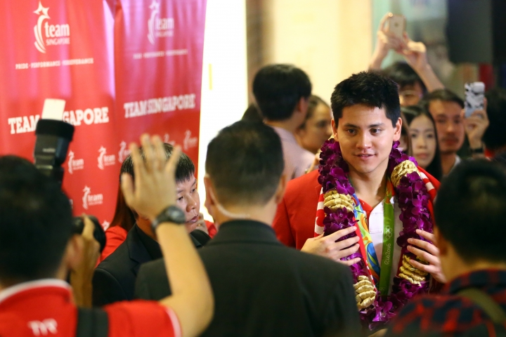 Singaporean swimmer Joseph Schooling is surrounded by media and people on his arrival at the Singapore Changi Airport in Singapore Monday, Aug. 15, 2016. Schooling won gold medal in the men's 100-meter butterfly and made history by winning the country's first gold medal at the 2016 Summer Olympics in Rio de Janeiro, Brazil. (AP Photo/Yong Teck Lim)