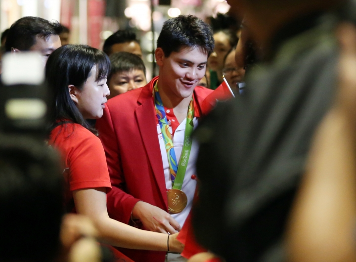 Singaporean swimmer Joseph Schooling, center, is surrounded by media and people on his arrival at the Singapore Changi Airport in Singapore Monday, Aug. 15, 2016. Schooling won gold medal in the men's 100-meter butterfly and made history by winning the country's first gold medal at the 2016 Summer Olympics in Rio de Janeiro, Brazil. (AP Photo/Yong Teck Lim)