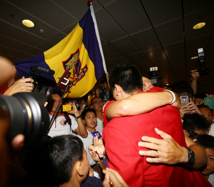 Singaporean swimmer Joseph Schooling, front center, is welcomed on his arrival at the Singapore Changi Airport in Singapore Monday, Aug. 15, 2016. Schooling won gold medal in the men's 100-meter butterfly and made history by winning the country's first gold medal at the 2016 Summer Olympics in Rio de Janeiro, Brazil. (AP Photo/Yong Teck Lim)