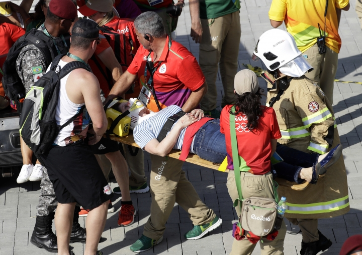 An injured woman is taken away on a backboard after being struck by an overhead television camera that fell from wires suspending it over Olympic Park during the Summer Games in Rio de Janeiro, Brazil, Monday, Aug. 15, 2016. A witness said the large camera, which moved back and forth along wires providing aerial views of the main Olympic park, was being examined on a bridge overlooking an arena entrance. The severity of her injury was not immediately clear. (AP Photo/Robert F. Bukaty)