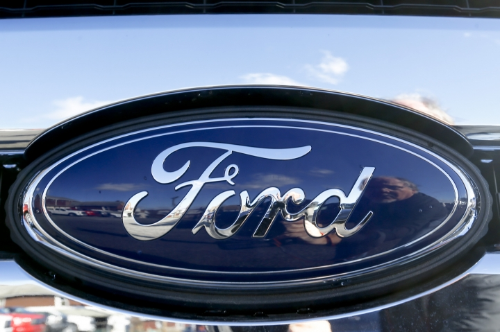 FILE - This Thursday, Nov. 19, 2015, file photo, shows the blue Ford oval badge in the grill of a pickup truck on the sales lot at Butler County Ford in Butler, Pa. Ford and Chinese search engine company Baidu announced Tuesday, Aug. 16, 2016, they will invest $75 million each in Velodyne, a company that makes laser sensors that help guide self-driving cars. (AP Photo/Keith Srakocic, File)