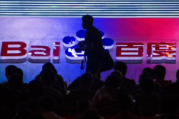 FILE - In this Sept. 2, 2011, file photo, a photographer walks past the logo of Baidu Inc. during a technology innovation conference held by the company at China's National Convention Center in Beijing. Ford and Chinese search engine company Baidu announced Tuesday, Aug. 16, 2016, they will invest $75 million each in Velodyne, a company that makes laser sensors that help guide self-driving cars. (AP Photo/Alexander F. Yuan, File)