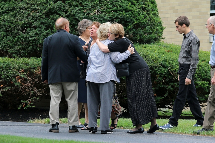 Mourners console each other outside Our Lady of the Lake Roman Catholic church as they arrive for her funeral service for Vanessa Marcotte, Tuesday, Aug. 16, 2016, in Leominster, Mass. Marcotte, 27, who worked for Google in New York City, was killed Aug. 7, while out running near her mother's Massachusetts home. Investigators have received more than 600 tips, but no arrests have been announced. They say her male assailant may have suffered cuts, scratches and bruises from a struggle. (John Love/The Sentinel & Enterprise via AP)