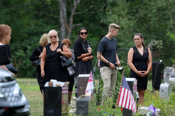 Mourners watch during the graveside service for Vanessa Marcotte at Woodside Cemetery Tuesday, Aug. 16, 2016, in Westminster, Mass. Marcotte, 27, who worked for Google in New York City, was killed Aug. 7 while out running near her mother's Massachusetts home. Investigators have received more than 600 tips, but no arrests have been announced. They say her male assailant may have suffered cuts, scratches and bruises from a struggle. (John Love/The Sentinel & Enterprise via AP)