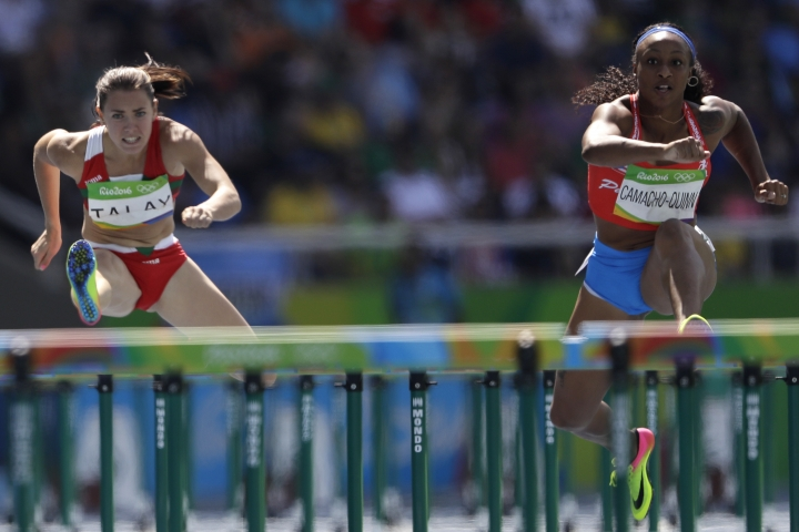 Puerto Rico's Jasmine Camacho-Quinn, right, and Belarus' Alina Talay compete in a women's 100-meter heat during the athletics competitions of the 2016 Summer Olympics at the Olympic stadium in Rio de Janeiro, Brazil, Tuesday, Aug. 16, 2016. (AP Photo/David J. Phillip )