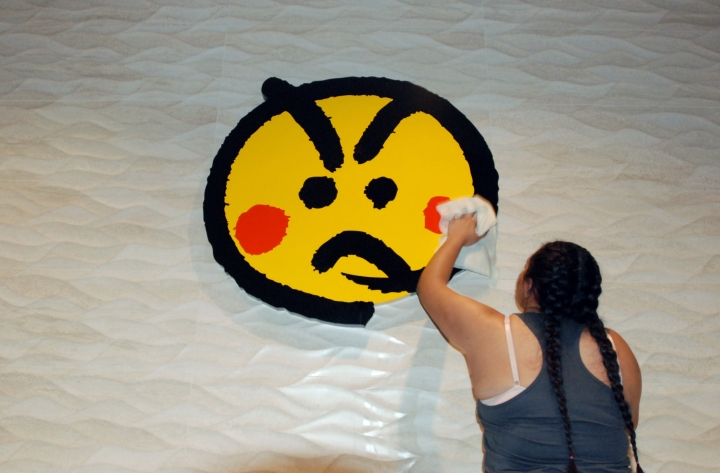 An employee cleans a logo at the Genki Sushi conveyor belt restaurant chain Tuesday, Aug. 16, 2016, in Aiea, Hawaii. The Hawaii State Department of Health Sanitation said Tuesday that Genki Sushi is being ordered to close its 10 restaurants on Oahu and one on Kauai after state authorities identified its raw scallops as the probable source of a hepatitis A outbreak. The disease can cause fever, loss of appetite and other symptoms. (AP Photo/Caleb Jones)