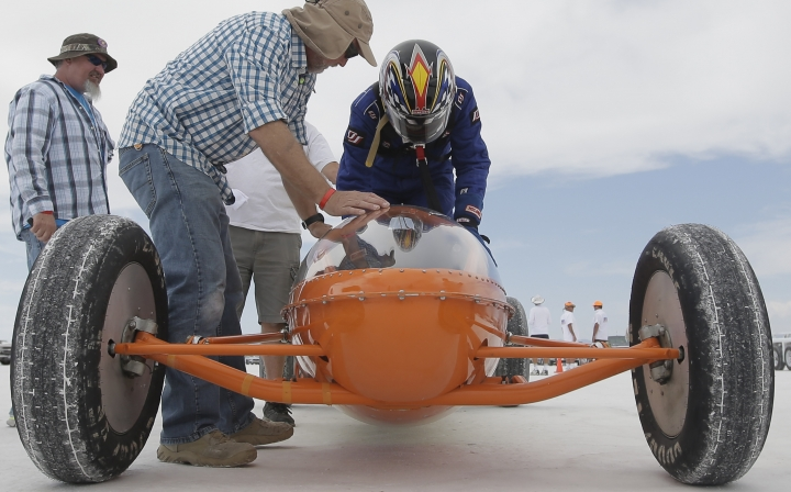 This Monday, Aug. 15, 2016, photo, driver Steve Nelson, of Petaluna, Ca, climbs into his vehicle at the Bonneville Salt Flats, near Wendover, Utah. Speed-starved racers are finally back at Utah's world-famous Bonneville Salt Flats to hit speeds of 400 mph or more as they compete in Speed Week for the first time since 2013 after wet weather and rough salt cancelled the races for the last two years. (AP Photo/Rick Bowmer)