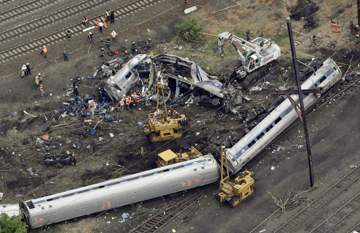 FILE- In this Wednesday, May 13, 2015 file photo, emergency personnel work at the scene of a derailment in Philadelphia of an Amtrak train headed to New York. Many commuter and freight railroads have made little progress installing safety technology designed to prevent deadly collisions and derailments despite a mandate from Congress, according to a government report released Wednesday, Aug. 17, 2016. (AP Photo/Patrick Semansky, File)