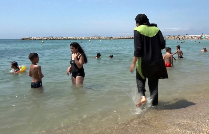 "FILE - In this Aug.4 2016 file photo made from video, Nissrine Samali, 20, gets into the sea wearing a burkini, a wetsuit-like garment that also covers the head, in Marseille, southern France. France's Socialist prime minister Manuel Valls is expressing support for local bans of burkinis, saying the swimwear is based on the ""enslavement of women"" and therefore not compatible with French values. (AP Photo, File)"