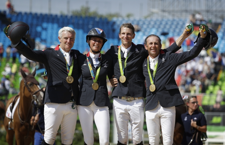 France's Roger Yves Bost, from left, Penelope Leprevost, Kevin Staut and Philippe Rozier celebrate after winning a gold medal in the equestrian team jumping competition at the 2016 Summer Olympics in Rio de Janeiro, Brazil, Wednesday, Aug. 17, 2016. (AP Photo/John Locher)