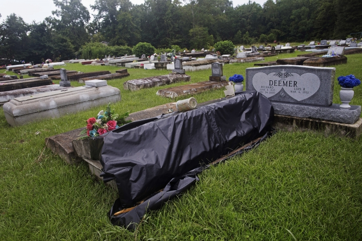A flood damaged tomb is covered for repair at the cemetery of Greater St. Mark Baptist Church in Walker, La., Tuesday, Aug. 16, 2016. Authorities went door to door and car to car to check for bodies Tuesday, and homeowners began the heartbreaking task of gathering up soaked family photos and mucking out houses dank with bayou mud, as the floodwaters started to recede across parts of southern Louisiana. (AP Photo/Max Becherer)