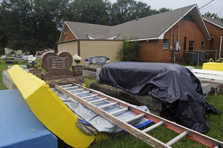 A coffin outside of a flood damaged tomb is covered to be resealed at the cemetery of Greater St. Mark Baptist Church in Walker, La., Tuesday, Aug. 16, 2016. Authorities went door to door and car to car to check for bodies Tuesday, and homeowners began the heartbreaking task of gathering up soaked family photos and mucking out houses dank with bayou mud, as the floodwaters started to recede across parts of southern Louisiana. (AP Photo/Max Becherer)