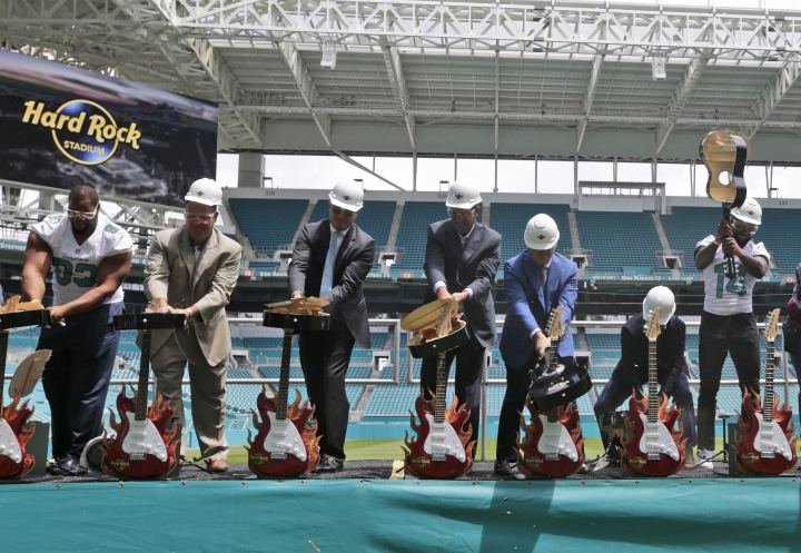 Miami Dolphins defensive tackle Ndamukong Suh (93), Mike Tannenbaum, executive vice president of football operations, second from left, and wide receiver Jarvis Landry (14) break guitars with other officials, Wednesday, Aug. 17, 2016, during a ceremony for a stadium naming rights agreement between the Miami Dolphins NFL football team and Hard Rock International, in Miami Gardens, Fla. The naming rights comes as the Dolphins near completion on a $500 million renovation that includes a canopy over the stands. (AP Photo/Lynne Sladky)