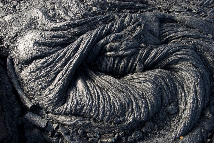 In this Monday, Aug. 8, 2016 photo, hardened lava rock from Kilauea, an active volcano on Hawaii's Big Island, is shown in Volcanoes National Park near Kalapana, Hawaii. The current lava flow erupted from a vent on the volcano in May and made its way to the sea in late July. Visitors can hike about 10 miles round trip to see the lava, or take a boat or helicopter tour to see the flow. (AP Photo/Caleb Jones)