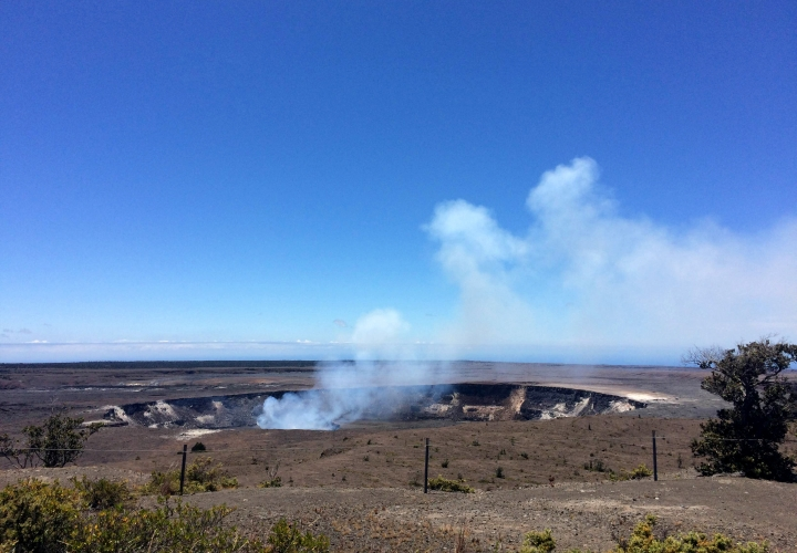 In this Monday, Aug. 8, 2016 photo, steam and gas rise from the summit crater atop Kilauea, an active volcano on Hawaii's Big Island, in Volcanoes National Park, Hawaii. The current lava flow erupted from a vent on the volcano in May and made its way to the sea in late July. Visitors can hike about 10 miles round trip to see the lava, or take a boat or helicopter tour to see the flow. (AP Photo/Caleb Jones)