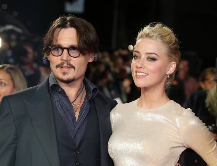 """FILE - In this Nov. 3, 2011 file photo, U.S. actors Johnny Depp, left, and Amber Heard arrive for the European premiere of their film, """"The Rum Diary,"""" in London. Heard says she is donating her entire $7 million divorce settlement from Depp to a pair of charities. Heard writes in a statement released Thursday, Aug. 18, 2016, that the money will be split between the American Civil Liberties Union and the Children's Hospital Los Angeles. (AP Photo/Joel Ryan, File)"""