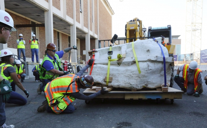 Encased in plaster, the 4-foot-long, 2,500-pound remains of a Tyrannosaurus rex skull, is moved by fork lift to a wheeled cart behind the loading dock of the Burke Museum on Thursday, Aug. 18, 2016 in Seattle. Paleontologists with Seattle's Burke Museum have unearthed the bones of a Tyrannosaurus rex that lived more than 66 million years ago, including a rare nearly complete 4-foot long skull. The remarkable discovery includes the carnivorous dinosaur's vertebrae, ribs, hips and lower jaw bones, and represents about 20 percent of the animal. (Alan Berner/The Seattle Times via AP)