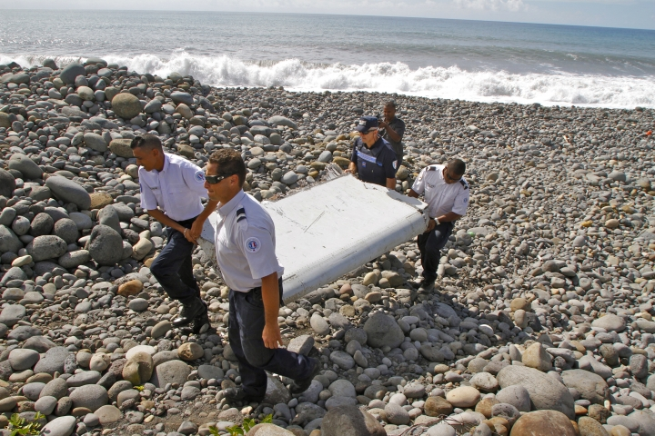 """FILE - In this July 29, 2015, file photo, French police officers carry a piece of debris from a plane known as a """"flaperon"""" on the shore of Saint-Andre, Reunion Island. An Australian official says experts hunting for the missing Malaysian airliner are attempting to define a new search area by studying where in the Indian Ocean the first piece of wreckage recovered from the lost Boeing 777 _ a wing flap _ most likely drifted from after the disaster that claimed 239 lives. (AP Photo/Lucas Marie, File)"""