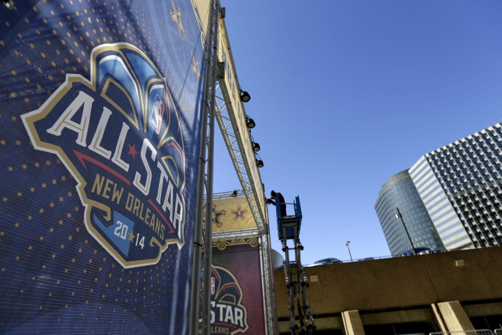 FILE - In this Feb. 13, 2014, file photo, a worker attaches a banner to a scaffolding in New Orleans in preparation of the NBA All-Star basketball game. The NBA has decided to hold the 2017 All-Star Game in New Orleans, a person familiar with the decision told The Associated Press. The person spoke to the AP on condition of anonymity Friday, Aug. 19, 2016, because the decision hasn't been announced. New Orleans replaces Charlotte, which was set to host the game until the NBA decided last month that it wouldn't hold its marquee, mid-season event in North Carolina because of a state law that limits anti-discrimination protections for lesbian, gay and transgender people. (AP Photo/Gerald Herbert, File)