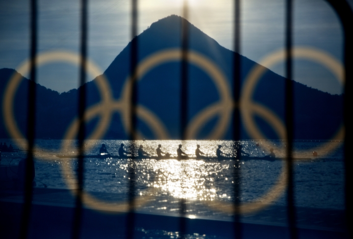 FILE - In this Aug. 7, 2016 file photo, rowers are seen through a screen decorated with the Olympic rings as they practice at the rowing venue in Lagoa at the 2016 Summer Olympics in Rio de Janeiro, Brazil. The night of Sunday, Aug. 21 will mark the launch of the Olympic Channel, designed to keep Olympic sports relevant between each games and bring young audiences into sports. The digital channel will go live right after the closing ceremony of the Rio Games, providing a mix of original programming, live sports events, news and highlights. (AP Photo/David Goldman, File)