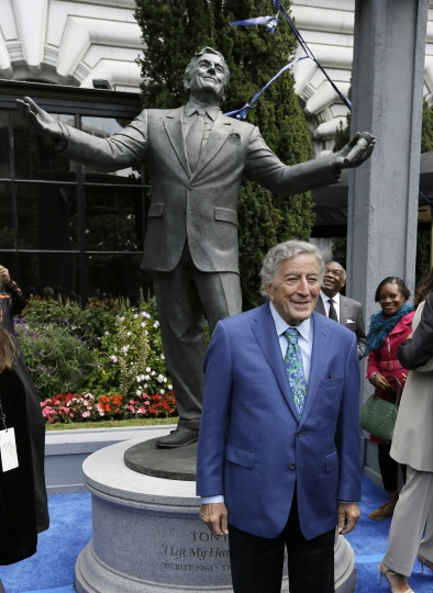 "Singer Tony Bennett stands beneath his 8-foot-tall bronze statue after it was unveiled outside the Fairmont Hotel Friday, Aug. 19, 2016, in San Francisco. Bennett arrived to a standing ovation by hundreds of well-wishers and a jazz combo wishing him a very ""Happy Birthday,"" to celebrate Bennett's 90th birthday. (AP Photo/Eric Risberg)"