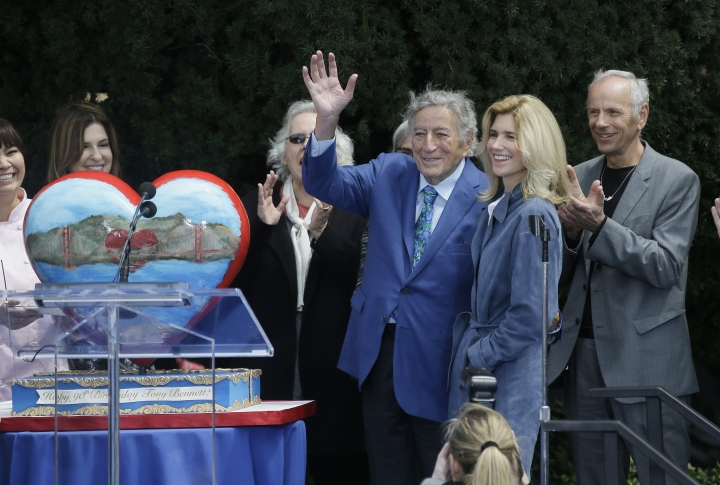 "Tony Bennett waves while standing with his wife, Susan Crow, after he was presented with a heart shaped birthday cake outside the Fairmont Hotel Friday, Aug. 19, 2016, in San Francisco. Hundreds gathered to celebrate Bennett's 90th birthday with the unveiling of an 8-foot-tall bronze statue of the singer atop Nob Hill. Bennett first sang ""I Left My Heart in San Francisco"" at the Fairmont Hotel in 1961. (AP Photo/Eric Risberg)"