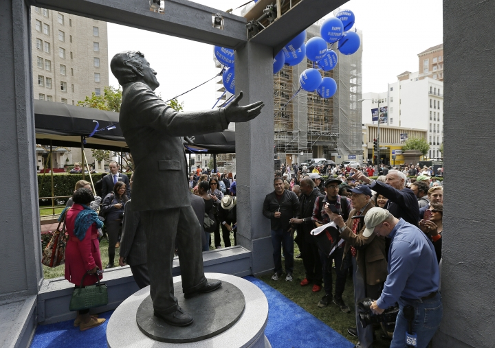 People gather near a statue of music icon Tony Bennett after it was unveiled outside the Fairmont Hotel, Friday, Aug. 19, 2016, in San Francisco. Bennett, who was present at the unveiling, turned 90 on Aug. 3. (AP Photo/Eric Risberg)