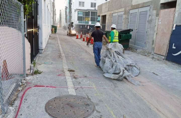 Miami Beach Sanitation workers clean up any sort trash that could hold water which allows mosquito larvae to grow, as another workers sucks up debris with mobile vacuum mobile in the alleyways of South Beach, Friday, Aug. 19, 2016, Miami Beach, Fla. (C.M. Guerrero/El Nuevo Herald via AP)