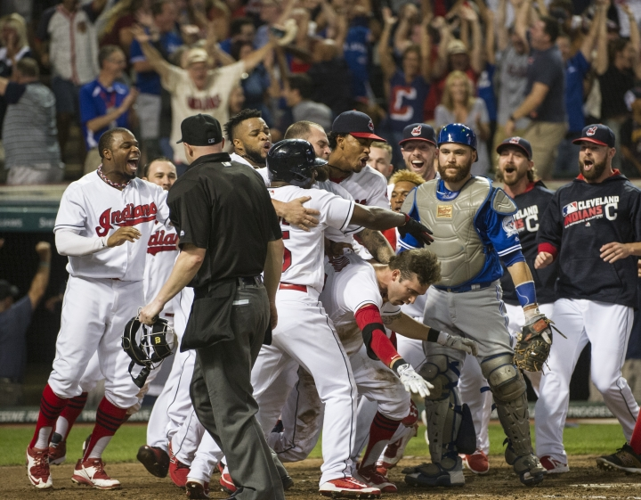 Cleveland Indians' Tyler Naquin, center with red sleeve, is mobbed by his teammates after hitting an inside-the-park home run off Toronto Blue Jays relief pitcher Roberto Osnuo for the game-winning run during a baseball game in Cleveland, Friday, Aug. 19, 2016. Caught in the mob is Blue Jays catcher Russell Martin. The Indians won 3-2. (AP Photo/Phil Long)