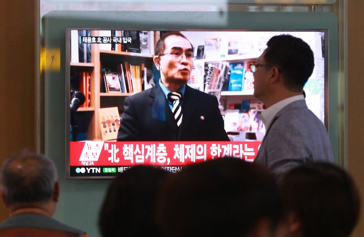 """FILE - In this Wednesday, Aug. 17, 2016 file photo, people watch a TV news program showing a file image of Thae Yong Ho, a minister at the North Korean Embassy in London, at Seoul Railway Station in Seoul, South Korea. North Korea on Saturday, Aug. 20, 2016, said Thae, a senior North Korean diplomat who recently defected to South Korea, is a criminal and """"human scum,"""" in its first official response to the defection. The letters read """"A high-ranking North Korean diplomat."""" (AP Photo/Ahn Young-joon. File)"""