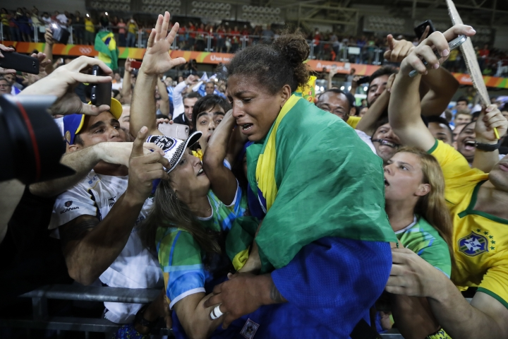 FILE - In this Aug. 8, 2016 file photo, Brazil's Rafaela Silva, centre, celebrates after winning the gold medal of the women's 57-kg judo competition at the 2016 Summer Olympics in Rio de Janeiro, Brazil. (AP Photo/Markus Schreiber, File)