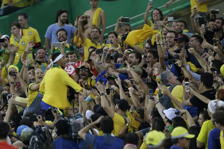 Brazil's Neymar celebrates with fans after the medal ceremony of the final match of the mens's Olympic football tournament between Brazil and Germany at the Maracana stadium in Rio de Janeiro, Brazil, Saturday Aug. 20, 2016. Brazil won the gold medal on penalty shoot-out. (AP Photo/Leo Correa)