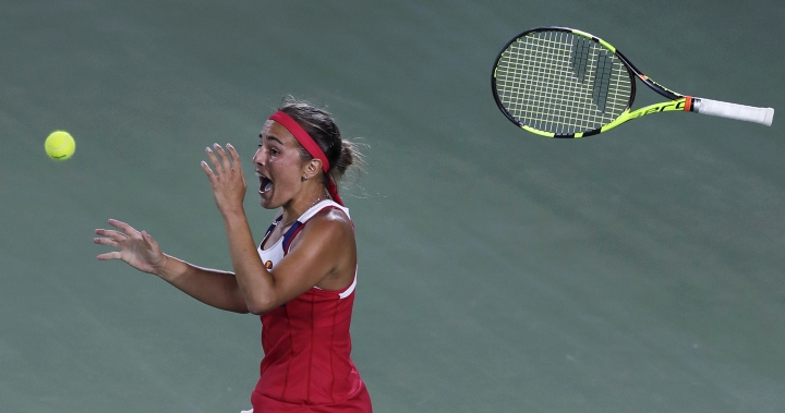 FILE - In this Aug. 13, 2016 file photo, Monica Puig, of Puerto Rico, tosses her racquet and celebrates after winning the gold medal against Angelique Kerber, of Germany, during the final round at the 2016 Summer Olympics in Rio de Janeiro, Brazil. (AP Photo/Charles Krupa, File)