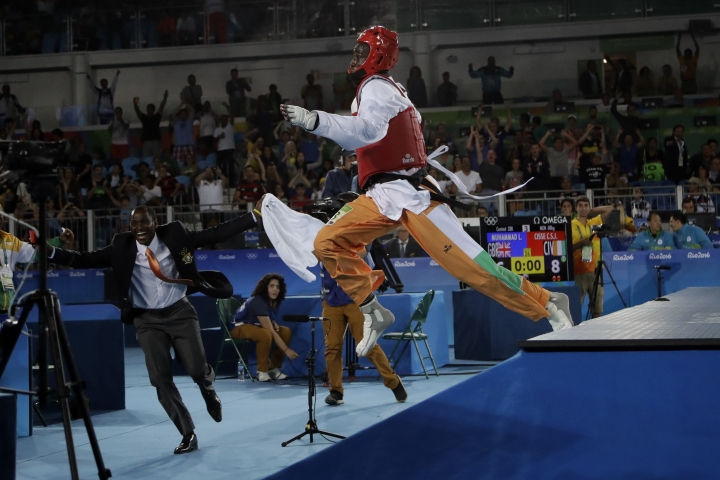 Cheick Sallah Junior Cisse of Ivory Coast jumps off the playing field after defeating Lutalo Muhammad of Great Britain in the final seconds of the men's 80 kg taekwondo gold medal contest at the 2016 Summer Olympics in Rio de Janeiro, Brazil, Friday, Aug. 19, 2016. (AP Photo/Gregory Bull)