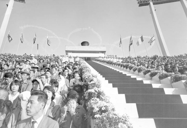 FILE - In this Oct. 10, 1964 file photo, five interlocking Olympic rings is thrown high in the sky by jet planes drift over the stadium during the opening ceremonies for the 1964 Olympics at the National Stadium in Tokyo. The next three Olympics are headed for relatively calmer ports of call in South Korea, Japan and China following the organizational drama surrounding the 2014 Winter Olympics in Russia and the just completed Summer Games in Brazil, but challenges remain, especially when it comes to finances and generating enthusiasm among home audiences. (AP Photo/File)