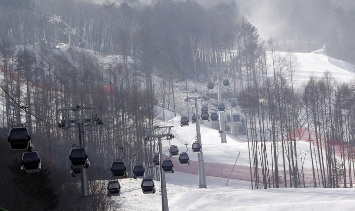 FILE - In this Jan. 22, 2016 file photo, gondolas make their way overhead near the ski slope which will be the venue for the upcoming official Test Event of the Pyeongchang 2018 Winter Olympics at the Jeongseon Alpine Centre in Jeongseon, South Korea. The next three Olympics are headed for relatively calmer ports of call in South Korea, Japan and China following the organizational drama surrounding the 2014 Winter Olympics in Russia and the just completed Summer Games in Brazil, but challenges remain, especially when it comes to finances and generating enthusiasm among home audiences. (AP Photo/Lee Jin-man, File)