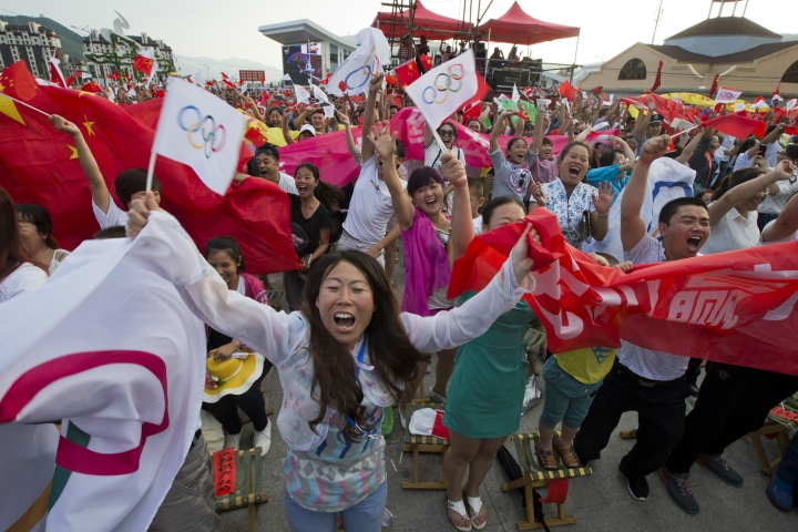 FILE - In this July 31, 2015, file photo, residents celebrate as Beijing is announced as the host city for the 2022 Winter Olympics at the ski resort region of Chongli where the Nordic skiing, ski jumping, and other outdoor Olympic events will be held in northern China's Hebei province. The next three Olympics are headed for relatively calmer ports of call in South Korea, Japan and China following the organizational drama surrounding the 2014 Winter Olympics in Russia and the just completed Summer Games in Brazil, but challenges remain, especially when it comes to finances and generating enthusiasm among home audiences. (AP Photo/Ng Han Guan, File)
