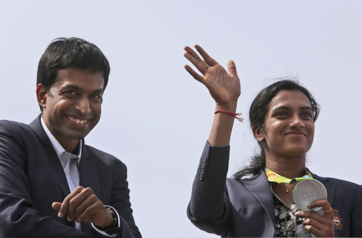 Pusarla Sindhu, right, one of the only two Indians to win medals at the just concluded Rio Olympics, displays her silver medal as she is brought home in a procession along with her coach, Pullela Gopichand, upon their arrival in Hyderabad, India, Monday, Aug. 22, 2016. Sindhu won silver in women's singles badminton. (AP Photo/ Mahesh Kumar A)