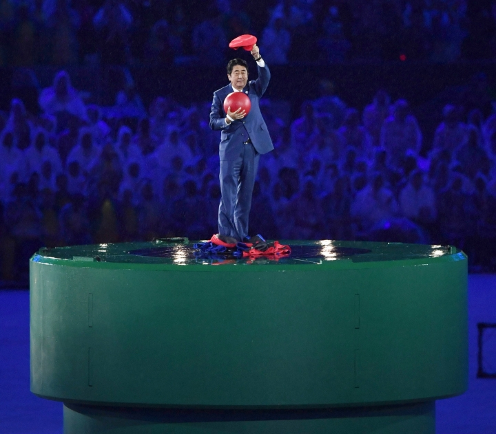 Japanese Prime Minister Shinzo Abe poses just after removing the costume of the Nintendo game character Super Mario as he makes an appearance during the closing ceremony at the 2016 Summer Olympics in Rio de Janeiro, Brazil, Sunday, Aug. 21, 2016. Abe's brief but show-stopping appearance as Super Mario offered a tantalizing glimpse at Tokyo's plans for the 2020 games. (Yu Nakajima/Kyodo News via AP)