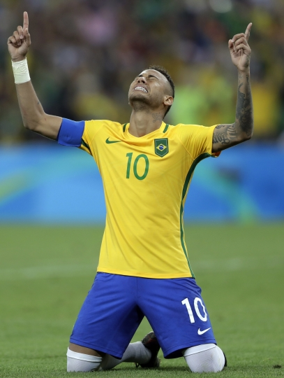 Brazil's Neymar weeps as he kneels down to celebrate after scoring the decisive penalty kick during the final match of the men's Olympic football tournament between Brazil and Germany at the Maracana stadium in Rio de Janeiro, Brazil, Saturday Aug. 20, 2016. Brazil won the gold medal on a penalty shootout. (AP Photo/Andre Penner)