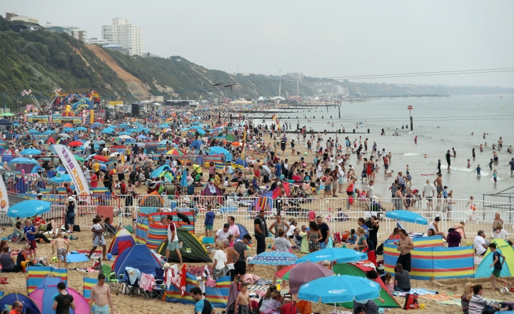 FILE - In this Thursday Aug. 18, 2016, file photo, people gather on a public beach in Bournemouth, England. Global travel spending is still growing, although at a slower pace, despite weakening economies and fears over terrorism, according to a report Monday, Aug. 22, 2016, by the World Travel and Tourism Council. Growth in the United Kingdom is actually expected to exceed the rest of Europe, in 2016. (Andrew Matthews/PA via AP, File)