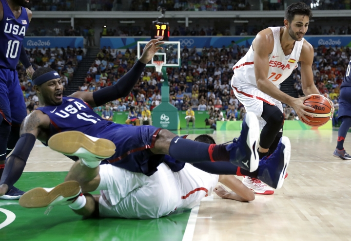 United States' Carmelo Anthony (15) falls over Spain's Felipe Reyes (9) as Spain's Ricky Rubio (79) grabs a loose ball during a men's semifinal round basketball game at the 2016 Summer Olympics in Rio de Janeiro, Brazil, Friday, Aug. 19, 2016. (AP Photo/Eric Gay)