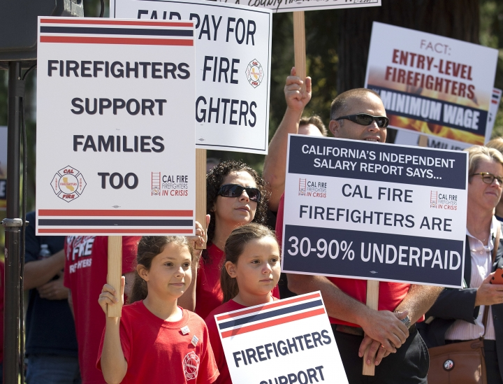 Jason Morris, right, a fire captain of the California Department of Forestry and Fire Protection, joined by his wife, Rosie, left, and daughters Ashlynn, 8, left, and Brianna, attends a rally calling for shorter hours and higher wages to retain firefighters, at the Capitol, Monday, Aug. 22, 2016, in Sacramento, Calif. Statistics provided to The Associated Press show vacancy rates exceeding 15 percent in some CaliFire positions. (AP Photo/Rich Pedroncelli)