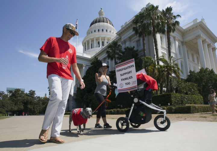 Ryan Mitchell, a fire captain with the California Department of Forestry and Fire Protection, from San Diego, joined by his wife, Denelle, son Aiden, 3 months and dog, Oso, joins other firefighters and supporters at a rally calling for shorter hours and higher wages to retain firefighters, at the Capitol, Monday, Aug. 22, 2016, in Sacramento, Calif. Statistics provided to the Associated Press show vacancy rates exceeding 15 percent in some CaliFire positions. (AP Photo/Rich Pedroncelli)