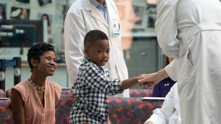 Zion Harvey, center, who received a double hand transplant in July 2015, shakes hands with a health care worker as his mother Pattie Ray, left, smiles during a news conference, Tuesday, Aug. 23, 2016 at The Children's Hospital of Philadelphia in Philadelphia. Zion Harvey talked about his progress since receiving a double hand transplant in July 2015, becoming the youngest hand transplant patient in the U.S., and now the boy from the Baltimore suburb of Owings Mills, Md., can throw a ball, zip his clothes and write in his journal. (AP Photo/Dake Kang)