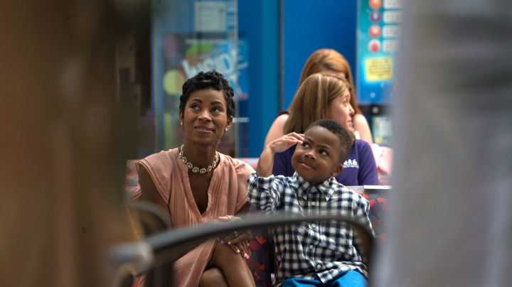 Zion Harvey, front right, who received a double hand transplant in July 2015, raises his right arm while sitting next to his mother Pattie Ray, left, during a news conference Tuesday, Aug. 23, 2016 at The Children's Hospital of Philadelphia in Philadelphia. Zion Harvey talked about his progress since receiving a double hand transplant in July 2015, becoming the youngest hand transplant patient in the U.S., and now the boy from the Baltimore suburb of Owings Mills, Md., can throw a ball, zip his clothes and write in his journal. (AP Photo/Dake Kang)