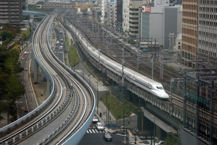 FILE - In this Sept. 24, 2014, file photo, a Shinkansen bullet train heads for Tokyo Station on the Tokaido Main Line in Tokyo. The countdown to the 2020 Olympics began Wednesday, Aug. 24, 2016, with the arrival of the Olympic flag in Tokyo from Rio de Janeiro. When Tokyo hosted the Summer Games in 1964 they were a symbol of Japan's recovery from World War II. The shinkansen bullet train began service in '64 in time for the Games and become a symbol of Japan's technological prowess. (AP Photo/Shizuo Kambayashi, File)