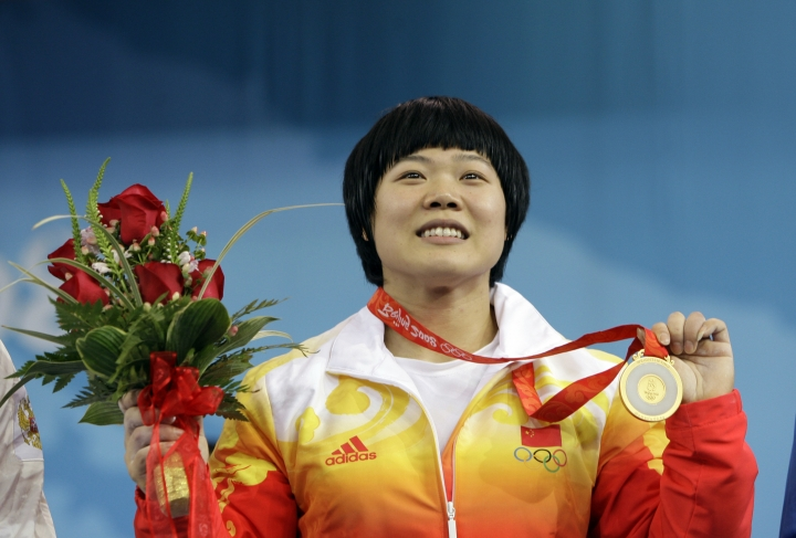 FILE - In this Wednesday, Aug. 13, 2008, file photo, Liu Chunhong, of China displays her gold medal in the women's 69 kg of the weightlifting competition at the Beijing 2008 Olympics in Beijing, China. The International Weightlifting Federation on Wednesday, Aug. 24, 2016, said that 11 2008 Olympic athletes tested positive in retests, including Liu, for a range of banned substances in the latest scandal to shake the sport, which is already processing retests which caught numerous medalists from the 2008 and 2012 games. (AP Photo/Andres Leighton, file)