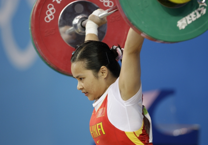 FILE - In this Aug. 9, 2008, file photo, China's Chen Xiexia holds up 90kg in the snatch of the women's 48kg category of the weightlifting competition at the Beijing 2008 Olympics in Beijing, China. The International Weightlifting Federation on Wednesday, Aug. 24, 2016, said that 11 2008 Olympic athletes tested positive in retests, including Chen, for a range of banned substances in the latest scandal to shake the sport, which is already processing retests which caught numerous medalists from the 2008 and 2012 games. (AP Photo/Andres Leighton)