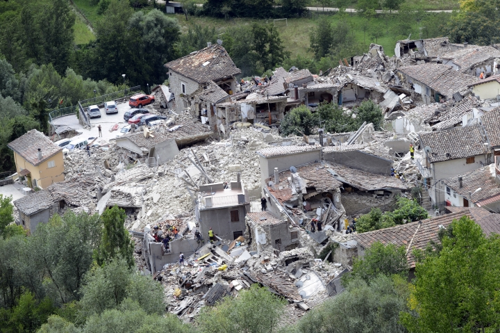 Rescuers search through debris of collapsed houses in Pescara del Tronto, Italy, Wednesday, Aug. 24, 2016. The magnitude 6 quake struck at 3:36 a.m. (0136 GMT) and was felt across a broad swath of central Italy, including Rome where residents of the capital felt a long swaying followed by aftershocks. (AP Photo/Sandro Perozzi)